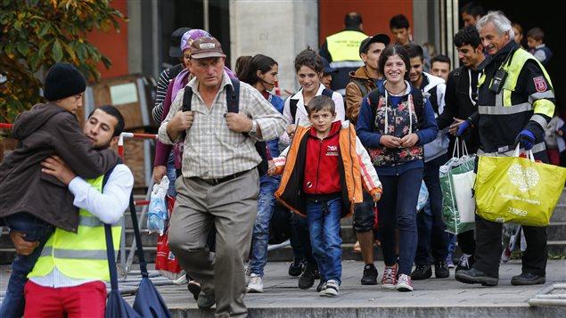 Des pompiers accueillent les migrants qui arrivent à Munich, en Allemagne.