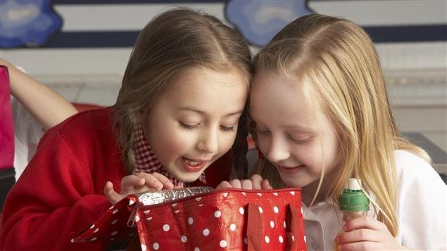 Deux petites filles inspectent le contenu d'une boîte à lunch.