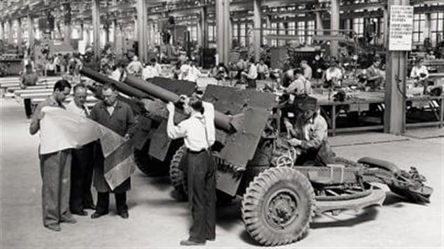 Workmen and engineers at the Sorel Industries Ltd look over blueprints of the 25-pounder field artillery piece. The giant SIL operation prouduced thousands of field artillery pieces, and naval and anti-aircraft guns and supplied barrels for the Sexton self-propelled guns prouced in Montreal at the two tank factories.