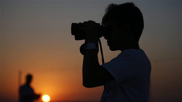 Un jeune utilise des jumelles pour surveiller la frontière syrienne.