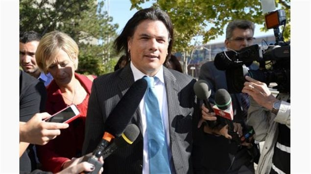 Senator Patrick Brazeau, a former member of the Conservative caucus, leaves the courthouse in Gatineau, Quebec on Tuesday after entering a guilty plea for charges on assault and possession of cocaine from incidents in 2013 and 2014. We see Brazeau, dressed in a dark pin-striped suit, white shirt and aqua-coloured tie, looking ahead as he is surrounded by a scrum of male and female reporters sticking microphones of all sizes in his face. Above his pale face and squinting eyes, lies long, black hair that is swept back. He wears a small earring in his right ear.