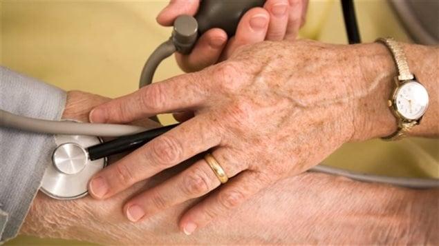 Un médecin donne des soins à un aîné.