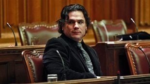 Patrick Brazeau was appointed to the Senate by Prime Minister Harper in 2008. We see Brazeau seated in the Senate wearing a dark jacket and fancy tie. A handsome man with long, black hair, he has his right arm resting on the desk in front of him as he looks to his right.