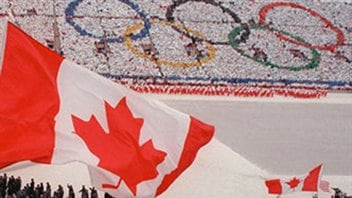 The opening of the 1988 Winter Olympic Games in Calgary. Is the city ready for an encore presentation? We see a giant Canadian flag in the foreground. Below the flag, athletes are marching into the stadium. In the background are fans holding cards to form the five Olympic rings.