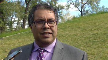 Calgary Mayor Naheed Nenshi says he wishes the city had made a bid for the 2022 Olympic Winter Games, and he confirms he has been part of conversations about the possibility of making a bid for the 2026 Games. We see a man of south-Asian complexion. He wears large glasses and a grey suit with a blue dress shirt and fancy tie. He is standing in front of a grassy mound and is appears to be listening to a question.