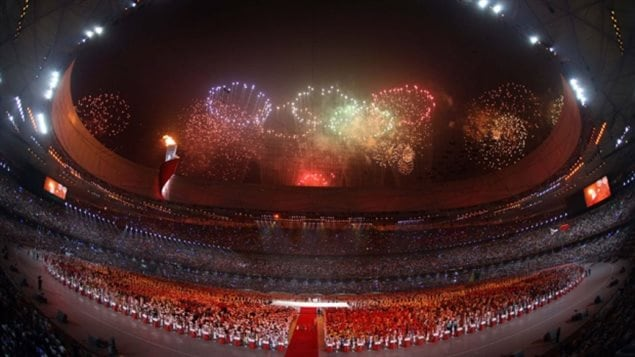 It looks like it will be a while before Canadians get to view an Olympic Games opening like this one in Beijing in 2008. We see a giant circular stadium with athletes gathered on the ground and the sky lit up with fireworks forming the five Olympic rings. The predominate colour of it all is red but blues and purples add to the mix.