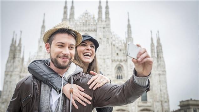 Un couple se photographie devant la cathédrale de Milan