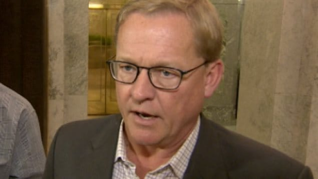 Alberta Education Minister David Eggen has the power to remove trustees on the Edmonton Catholic School Board but is waiting before he takes action. We see a sandy-haired man with large glasses dressed in a light, plaid shirt. He appears to be about to speak as his mouth is slightly agape.