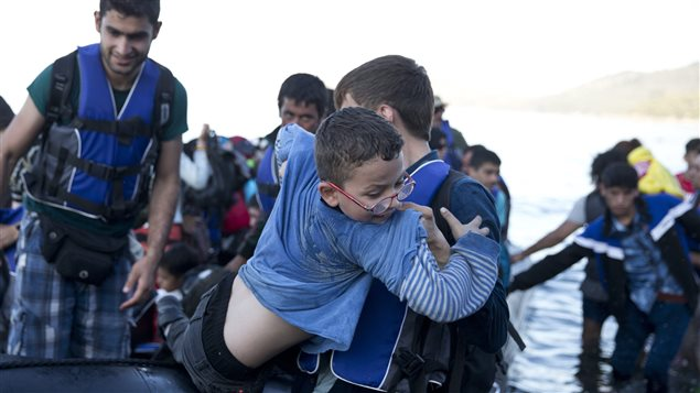 Syrian refugees arrive aboard a dinghy after crossing from Turkey today, to the island of Lesbos, Greece. More than 250,000 people have reached Greece clandestinely so far this year, the vast majority of them Syrians or Afghans fleeing conflict at home.