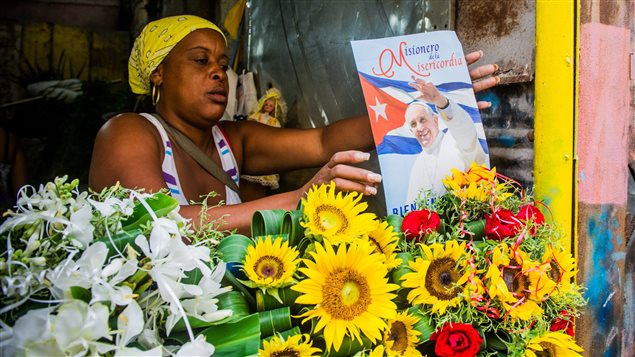 Une femme décore son balcon avec une affiche du pape François à La Havane, le 30 août 2015. Le pape visite l'île du 19 au 22 septembre.