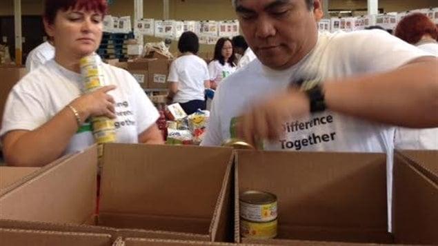 Des bénévoles placent des denrées dans des boîtes à la banque alimentaire Daily Bread de Toronto.