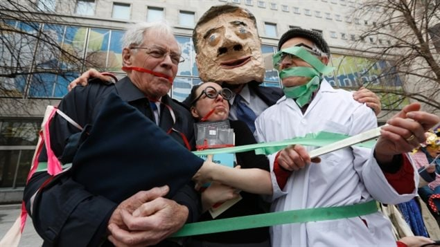 A group of protesters-- dressed as Canada's Prime Minister Stephen Harper, backbench Member of Parliament, a librarian and a scientist -- attend a demonstration against the muzzling of MPs and federal government employees in Ottawa in April 2013.