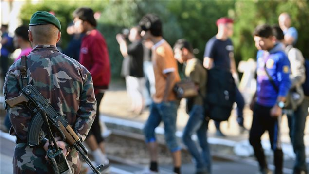 Migrantes que suben a un tren bajo la mirada vigilante de un soldado húngaro en la región de Magyarboly.