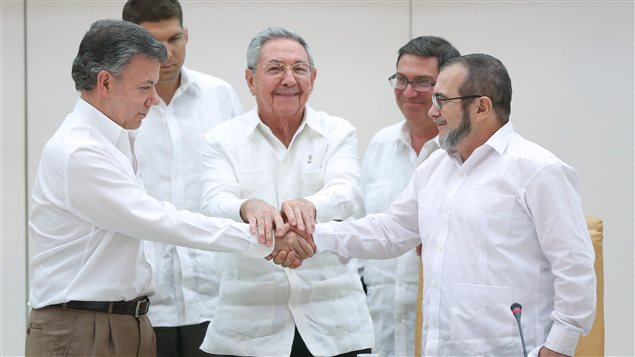 Le président cubain Raul Castro entre le président colombien Juan Manuel Santos (g) et le leader des FARC Rodrigo Londono (d)