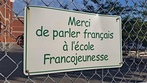 Une affiche sur laquelle on peut lire l'inscription «Merci de parler français à l'école Francojeunesse» est accrochée à une clôture devant l'École élémentaire publique Francojeunesse du Conseil des écoles publiques de l'Est de l'Ontario (CEPEO), située dans le secteur de la Côte-de-Sable, à Ottawa (archives).