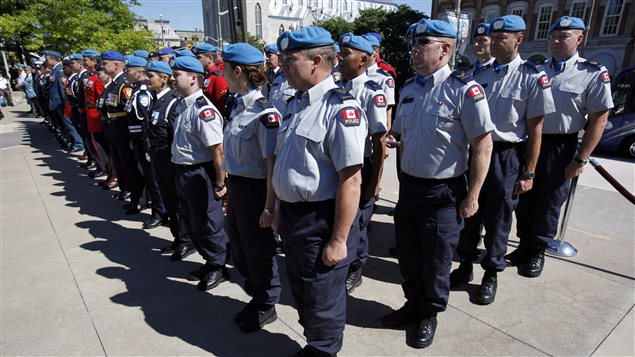 Canadian police officers training for a mission in Haiti stand at attention on National Peacekeepers Day August 11, 2013 in the nation's capital, Ottawa.