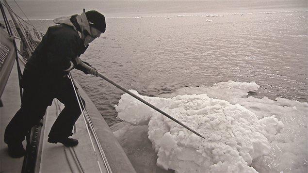 Un homme pousse des glaces avec un pieu.