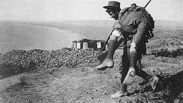 ANZAC solider carrying a wounded comrade back to the line with Anzac cove in the background