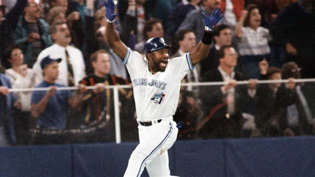 The last time the Blue Jays won a World Series was 1993 when Joe Carter (above) hit his famed three-run homer to deliver the victory. The Blue Jays are back in the playoffs for time since 1993 when Joe Carter (above) hit his dramatic home run against Philadelphia to win the World Series and send baseball fans across the country into ecstasy. The Jays are back this year for another crack. We see Carter is his white with blue trim uniform running down the first-base line with both hands in their blue batting gloves raised above his head and both feet off the ground as he ball heads for the left-field bleachers. His mouth is wide open, he is the picture of joy. In the background, it appears the fans cannot completely believe their eyes. They appear to be holding their collective breath. But Carter knows it is gone.