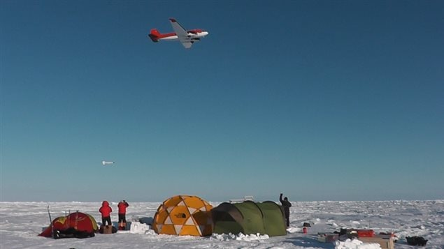 A research plane tows an electromagnetic sonsor (seen in the sky just above the two researchers in red) The equipment gives a far more reliable reading of ice thickness than can be ascertained from satellite readings.