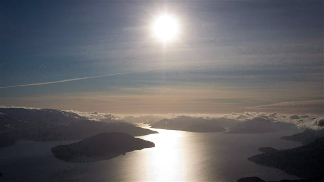 The Douglas Channel (above) is the proposed shipping route for oil tanker ships in the Enbridge Northern Gateway Project, just south of Kitimat, B.C. We see an absolutely gorgeous shot of water reflecting the bright glow of the sun. The water is surrounded by dark islands and mountains and white clouds. We see the sun high in the sky at the top centre of the photo, bright as a silver ball with rays extending from its edge.