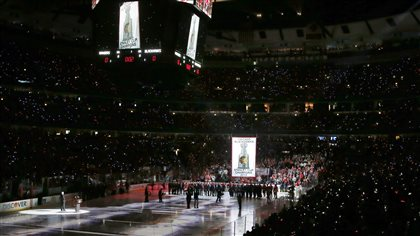 The Chicago Blackhawks' Stanley Cup championship banner is raised to the United Center ceiling during a ceremony before their game with the New York Rangers on Wednesday. The stands in the arena are aglow with cellphone lights reaching to the upper rafters. The ice blow reflects the flood lights (in streaks). At the far end, we see a lot of people is suits as the giant white banner makes its way up.