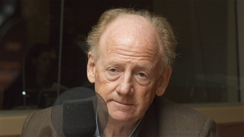 John Ralston Saul, a Canadian, is president of PEN International. We see Mr. Saul sitting behind a microphone. Balding but still retaining much of the blond in his hair, his face is deeply lined with babs under his eyes. He has something of a sad look on his face.