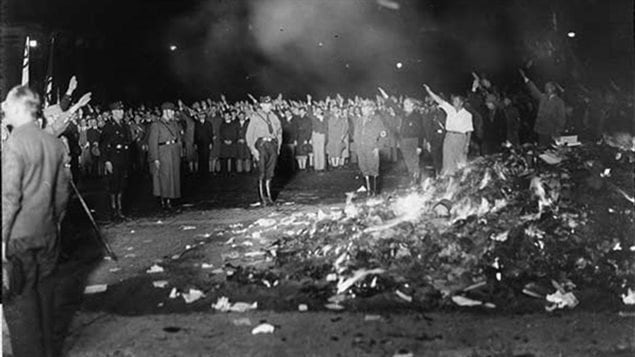 Fascist university students burned upwards of 25,000 books on the Opernplatz (Opera Square) in Berlin, Germany, on May 10, 1933. PEN International, long relentless in the fight for freedom of speech, is meeting this week in Quebec's capital. The black-and-white photo shows a huge pile of books aflame in the right foreground. Surrounding the the pyre are people dressed in military uniforms and  others in civilian dress. Many of the civilians have their right hands raised in the Nazi salute. The military figures stand at attention, one is saluting.