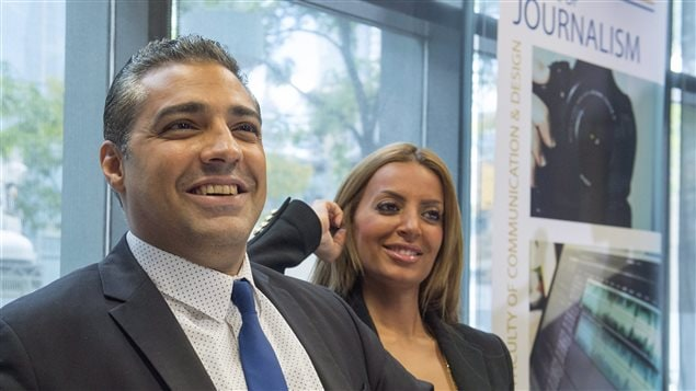 Mohamed Fahmy and his wife, Marwa Omara, are back in Canada following their long nightmare in Egypt. We see Fahmy on the right dressed in a classy, grey suit and blue tie, smiling in the left of the picture. His wife, to his left, has her right hand to her ear and is also smiling. Both appear ready for the rest of their life.