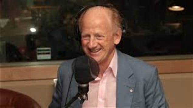 PEN International President John Ralston Saul, a Canadian, is concerned about the erosion of some freedoms in Canada. We see Mr. Saul, standing outside in front of microphone. he wears a suit jacket and open collar. He is smiling beneath is receding light brown hair and remains thin, appearing quite fit.
