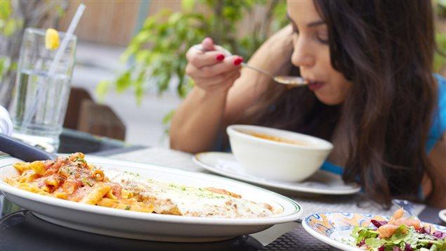 Une femme mange une soupe à l'extérieur.