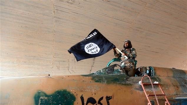 Un combattant brandit le drapeau du groupe armé État islamique.