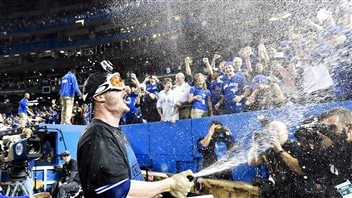 Toronto third baseman Josh Donaldson sprays champagne on fans in the wake of the Jays' series victory on Wednesday. We see Donaldson wearing googles and a dark championship tee-shirt with his mouth wide open in a shout spaying bubbles high into the air on fans in the stands and members of the press corps.
