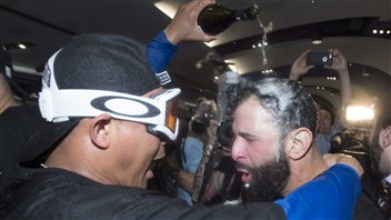 Utility player Ezequiel Carrera, left, douses slugger Jose Bautista with champagne after the Jays eliminated the Texas Rangers Wednesday night. Carrera, wearing celebration goggles, shouting with joy as he wraps his right arm around Bautista's shoulder and empties a bottle over Bautista's head with his left hand. The black bearded Bautista's hair is drenched and and his expression is one of woooofffff.