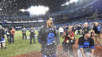 Wednesday's starting pitcher, Marcus Stroman, was--to say the least joyful--following the game. Stroman has his eyes closed and mouth wide open as champagne spray fills the air. In the background are security guards and cameramen.