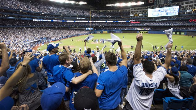 Toronto fans were ecstatic after the Wednesday's victory. In the seventh inning, not so much. We have a long shot from the back of the lower deck between home and first. Fans, many of them dressed in blue and white Jays jerseys and tee-shirts, have their arms raised in celebration, many of them hugging each other. In the distance gathered around the pitcher's mound at the centre of the green artificial turf, some winning Jays have gathered to celebrate as their teammates stream from the dugout the join them. We have a wide, circular shot of Rogers Centre, absolutely crammed with fans stands lit by the big overhead lights and the giant scoreboard.