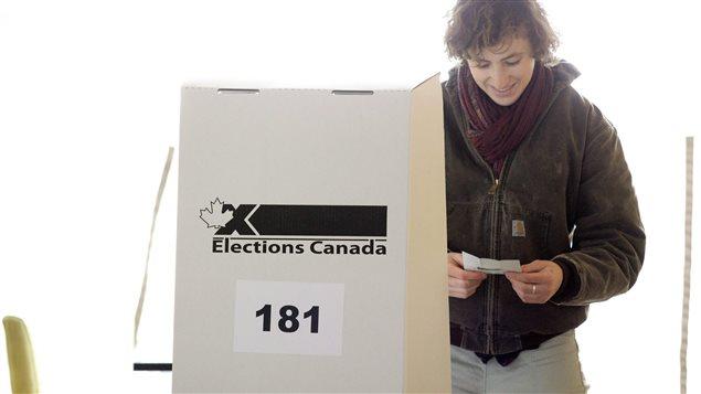Une femme de la région de Toronto examine son bulletin de vote (archives).