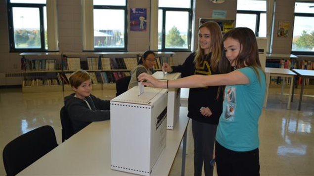 Des élèves de l'école secondaire des pionniers à Saint-Augustin-des-Desmaures, au Québec, déposent leur bulletin de vote.