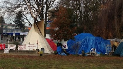Residents at the homeless protest camp in Jubilee Park in Abbotsford, shown in 2013. To the left the photo we see a white tee-pee shaped tent. On the right, we see a smaller, formless blue tent. The day is overcast and the grass in front of the tents looks very moist.