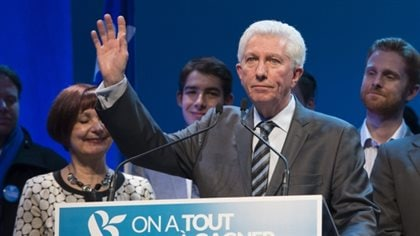 Bloc Québécois Leader Gilles Duceppe is getting out of politics. We see Mr. Duceppe in a grey suit and striped tie standing behind a podium waving with his right hand with pursed lips and a sad face. To his left, his wife, Yolande Brunelle, who had short, dark hair, stands. Her eyes are closed and she appears on the verge of tears. Behind the couple, several young men, likely family, appear to attempting not to show their sadness.