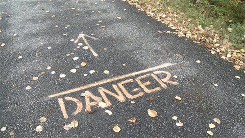 Un message annonce une zone cahoteuse sur une piste cyclable.