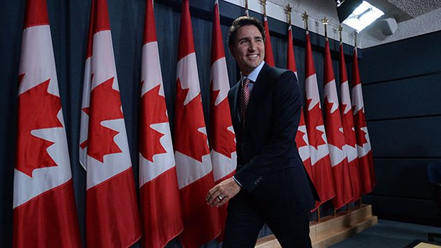 Justin Trudeau was all smiles after meeting the media on Tuesday. We see a lithe man in a dark suit in full stride with a wide smile leaving the press room. Behind him are about dozen red and white Canadian flags.