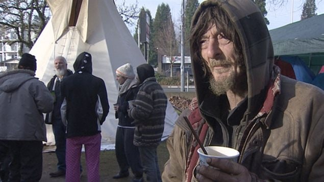 Residents at the homeless protest camp in Jubilee Park in 2014 refused to leave, despite threats of an injunction from the City of Abbotsford. We see in the right foreground an elderly man dressed in a beat-up army-like parka with the hood over his head. Over his brown goatee, he wears a faraway look in his eyes as he holds a styrofoam cup of coffee in his left hand. Behind him over his right shoulder several other men stand huddled in front of a white tent.