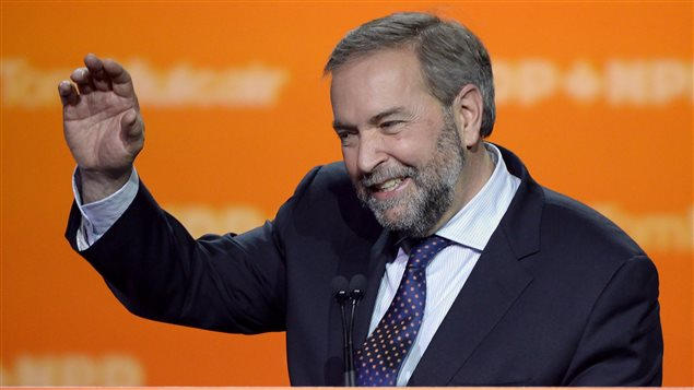 """NDP Leader Tom Mulcair speaks to supporters on Monday. He wants to remain as leader. We the bearded and greying Mulcair waving with his right hand as he stands in front of an orange backdrop on which are printed the words """"Tom Mulcair NDP-NPD."""" He appears to be smiling through very gritted teeth."""
