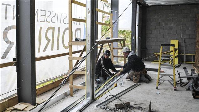 Les ouvriers utilisent des passerelles fixées à l'édifice plutôt qu'un échafaudage.