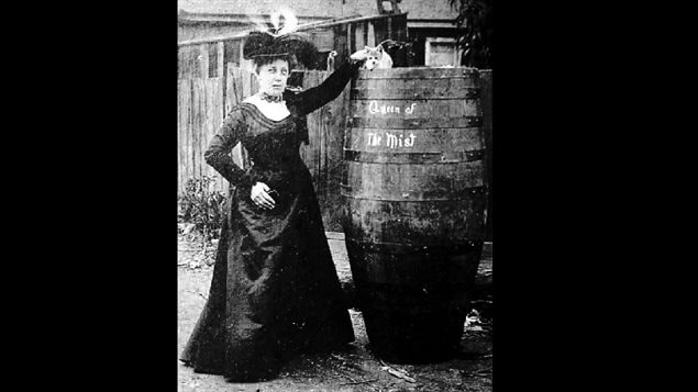 Annie Taylor poses in a backyard with a barrel and her hand on the cat, presumably which now has only 8 lives after surviving the