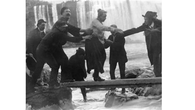 The shaken, slightly dazed, but alive and unharmed 63-year-old Annie Taylor being helped to shore after a rowboat pulled the barrel to the Candian side below the Falls.