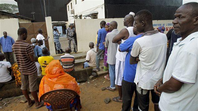 Des Ivoiriens attendent devant un bureau de vote à Abidjan, le 25 octobre 2015.