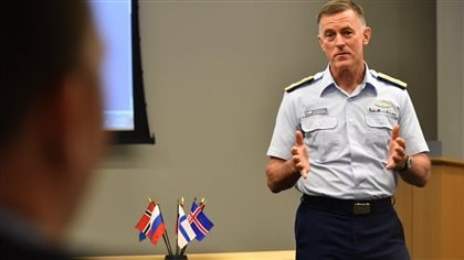 U.S. Coast Guard Commandant Adm. Paul Zukunft speaks during the Arctic Coast Guard Forum, at U.S. Coast Guard Headquarters in Washington, March 25, 2015. In the photo we see a man in coast guard uniform addressing an audience, standing next to a table with small flags of participating nations.