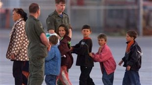 A Kosovar woman leads a parade of Kosovar children past Canadian soldiers at CFB Trenton after the plane full of refugees landed in May 1999. Canada is considering a massive airlift of Syrian refugees.